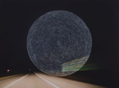 Photograph of a highway at night that has concentric circles scratched into the center of the image.